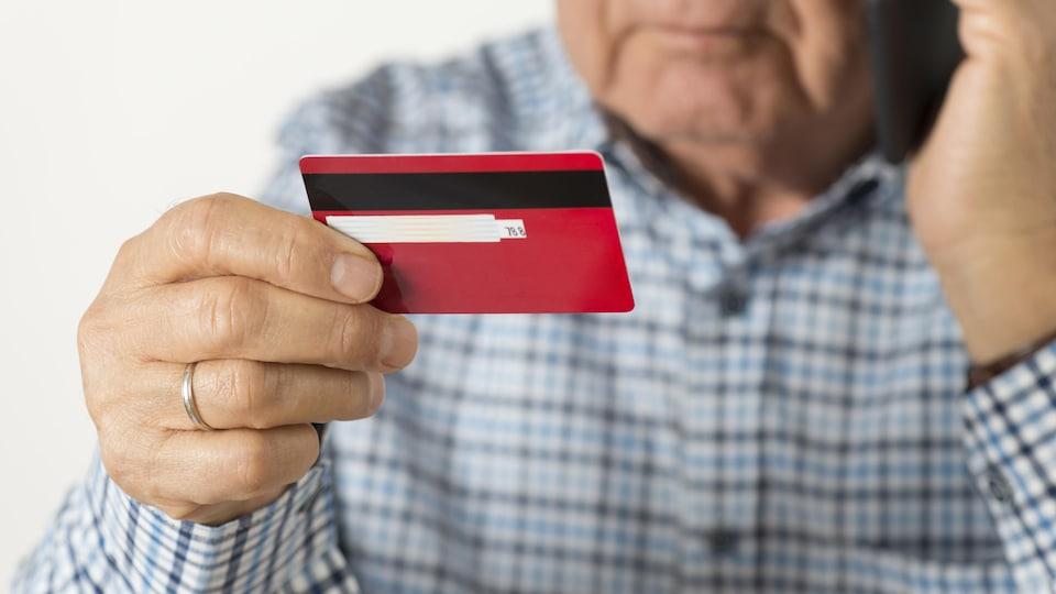 Un homme âgé parle au téléphone en tenant, dans son autre main, une carte de crédit.
