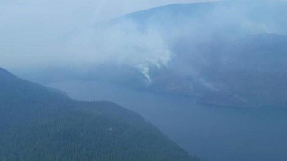 Un paysage de lac et de forêts est envahi par la fumée.