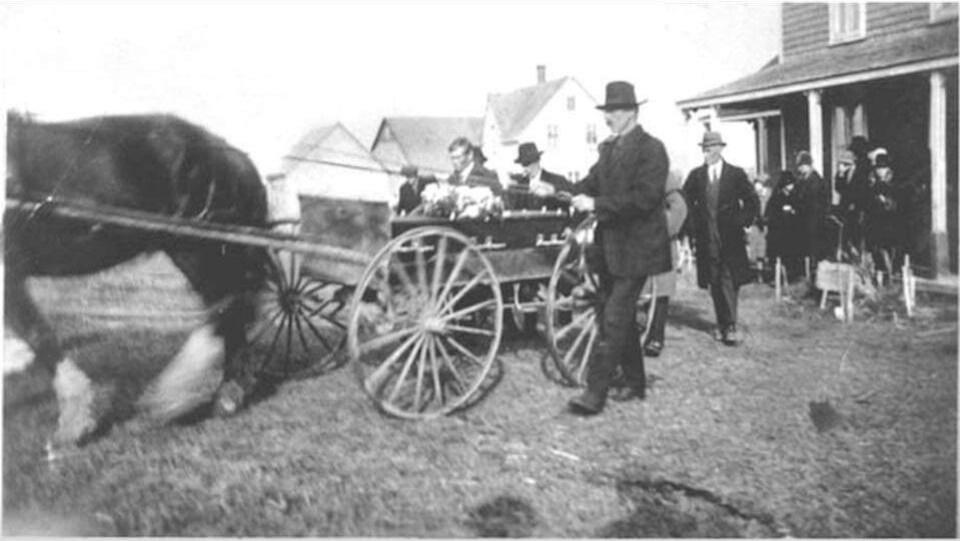 Ancienne photo montrant un cheval tirant un cercueil. Plusieurs personnes l'entourent.