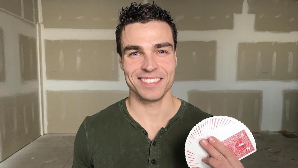 Roger Boucher dans une salle de répétition avec des cartes dans la main.