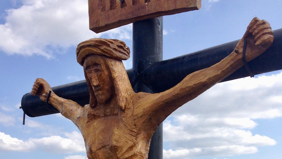 Une sculpture de Jésus sur une croix en bois.