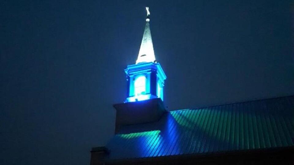 Le clocher de Zenon Park illuminé en bleu pendant la nuit.