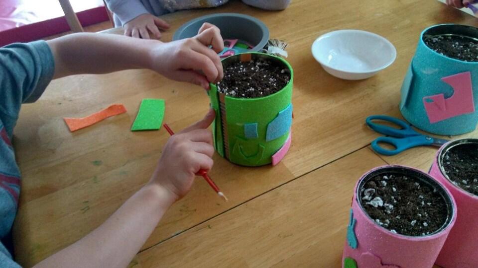 Des enfants décorent des pots de terre avec des morceaux de papier.