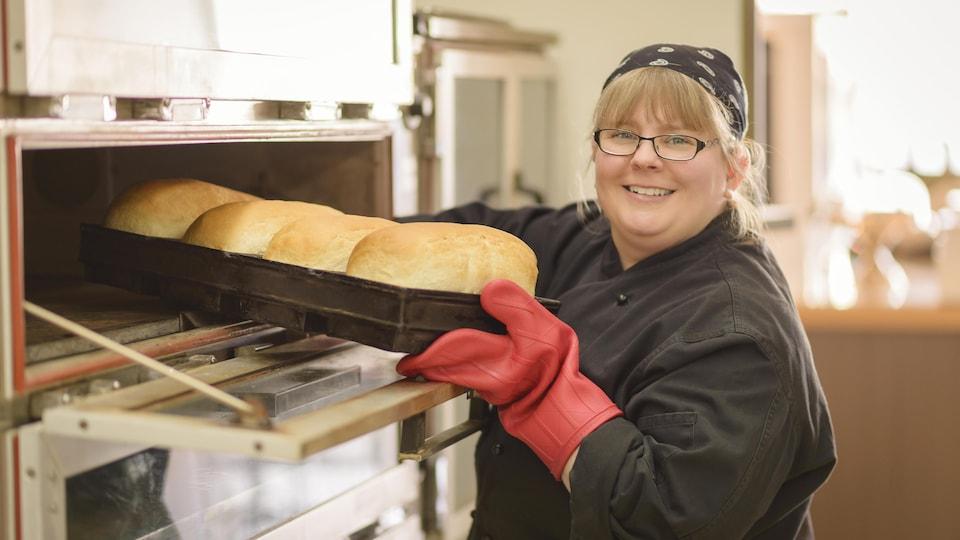 Caroline Bérubé sort du pain frais d'un four.