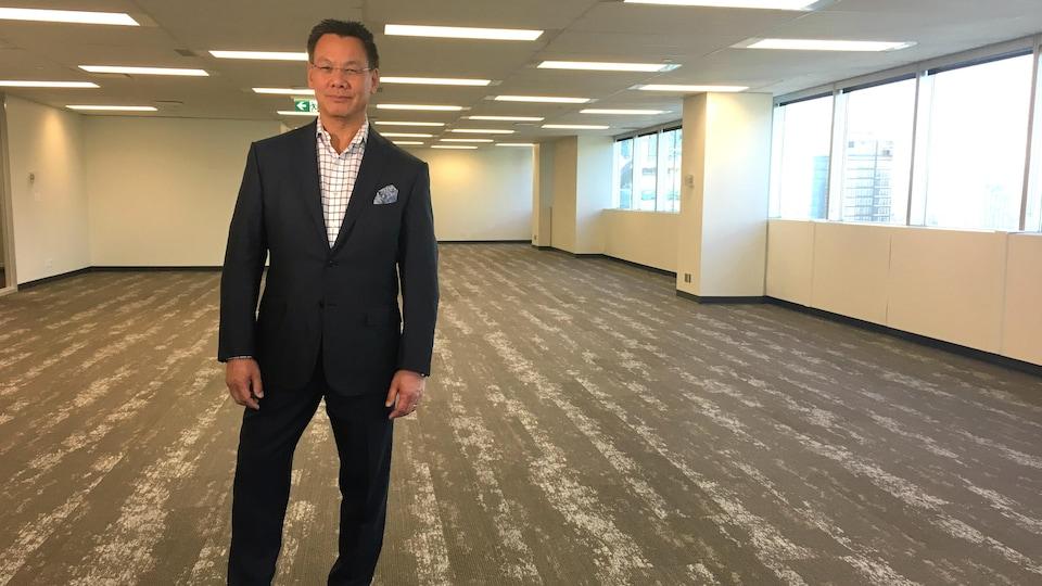 Un homme en costume se tient dans un espace de bureau complètement vide.