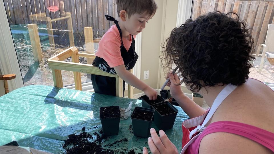 Une femme en train de faire du jardinage avec un jeune garçon.