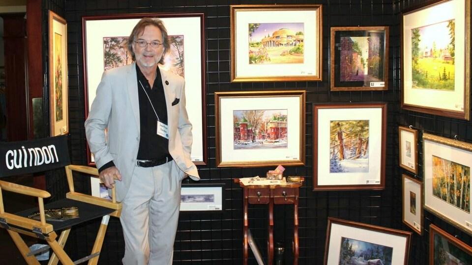 Jean-Yves Guidon est debout au milieu de plusieurs tableaux.