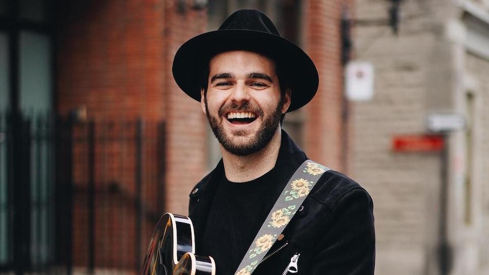 Guillaume Lafond, souriant, avec une guitare dans les mains.
