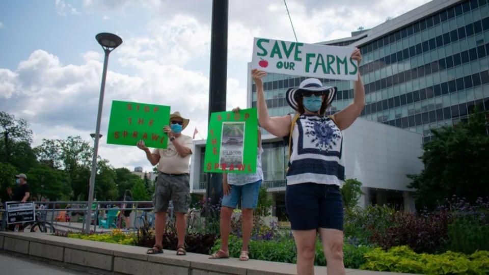 Trois manifestants tiennent des pancartes.