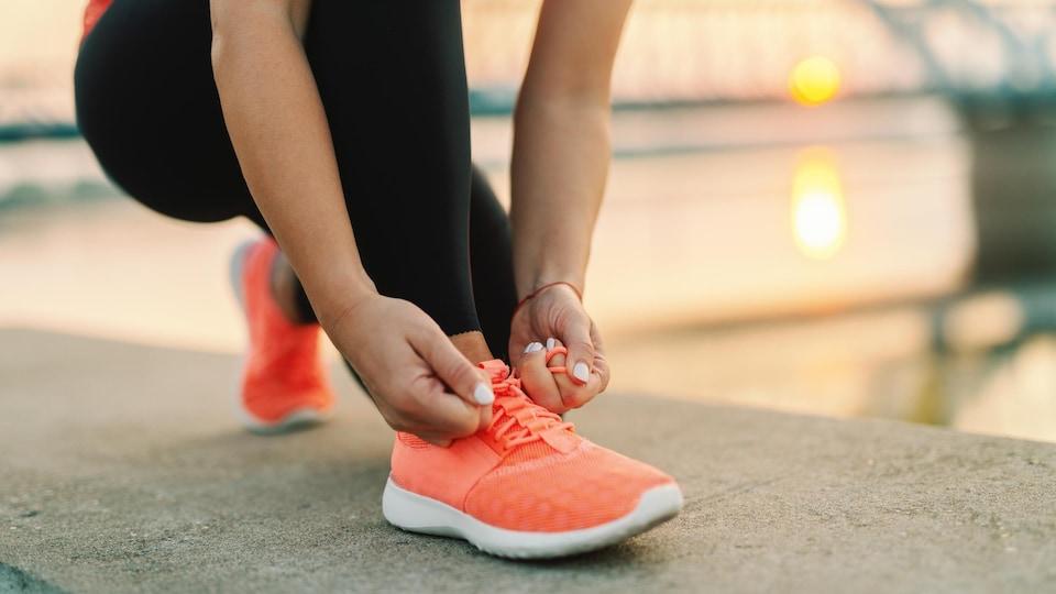 Au soleil couchant, une femme noue les lacets de son soulier de course.
