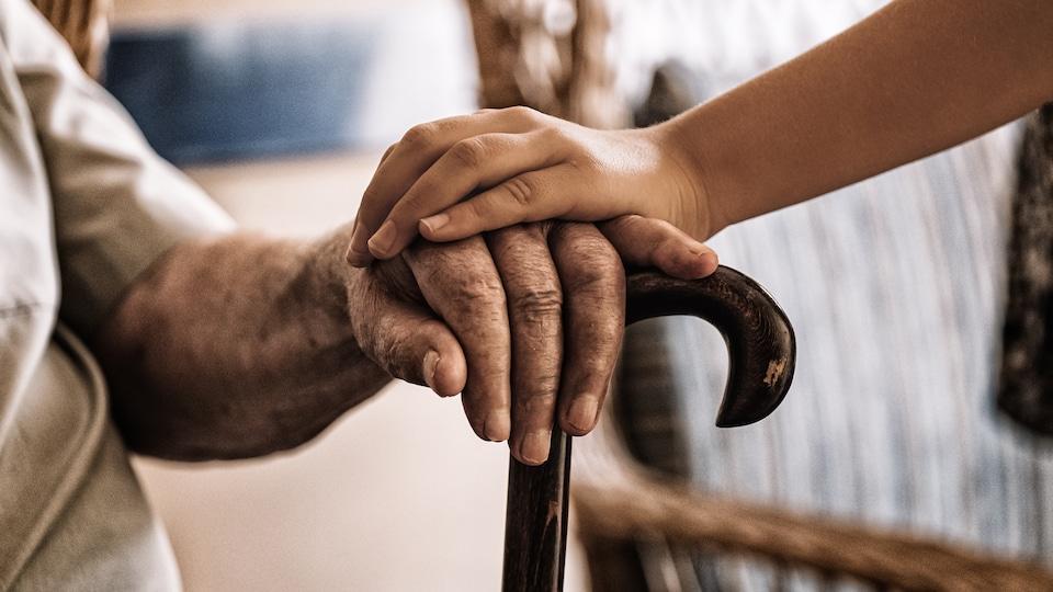 La main d'une jeune personne sur la main d'une personne âgée appuyée sur une canne.