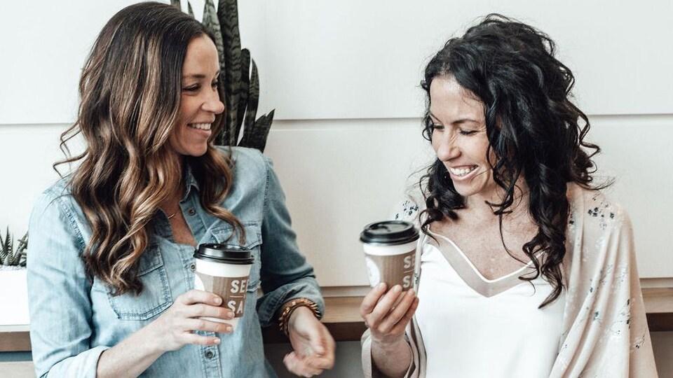 Les deux femmes sont assises sur des tabourets et tiennent des tasses de café estampillées de la marque de leur restaurant.