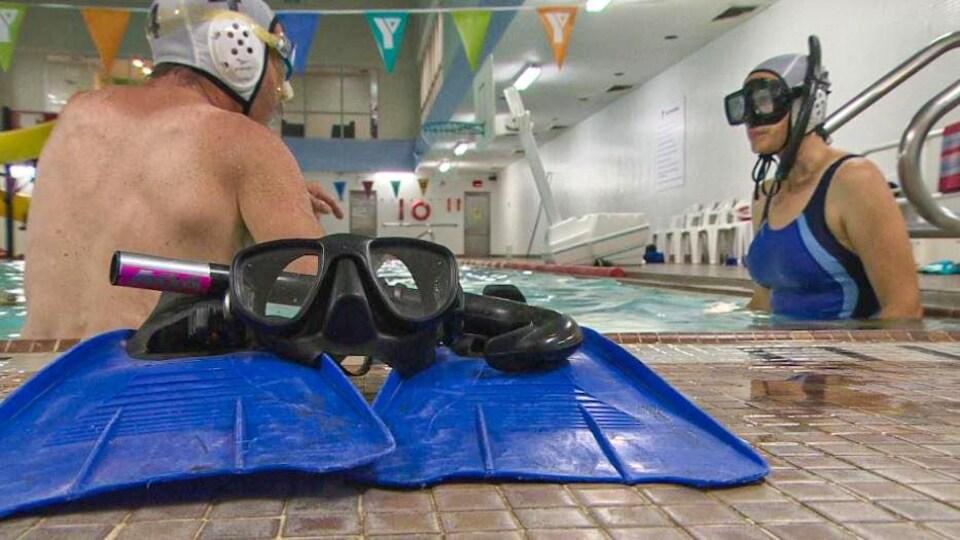 Des palmes et un masque sont au bord de la piscine.