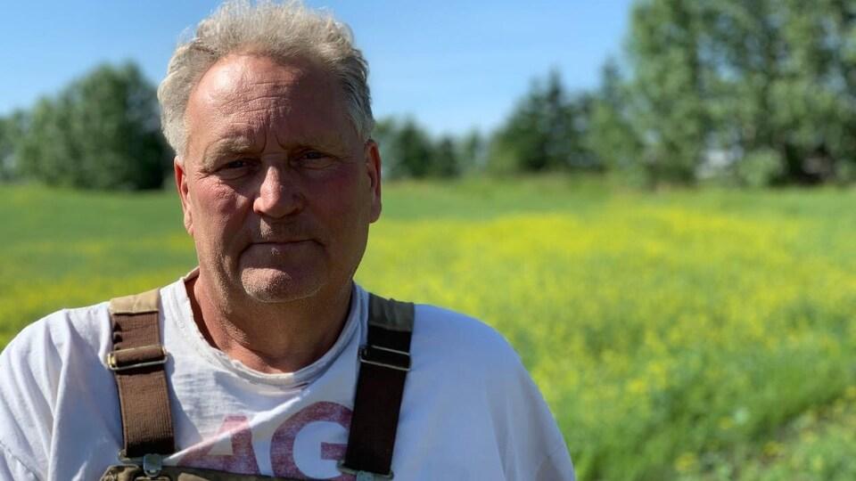 Humphrey Banack pose devant un champ de canola.