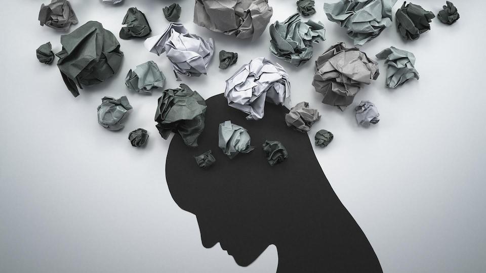 Illustration en papier d'une tête qui a des pensées troubles représentées par des boules de papier froissées.