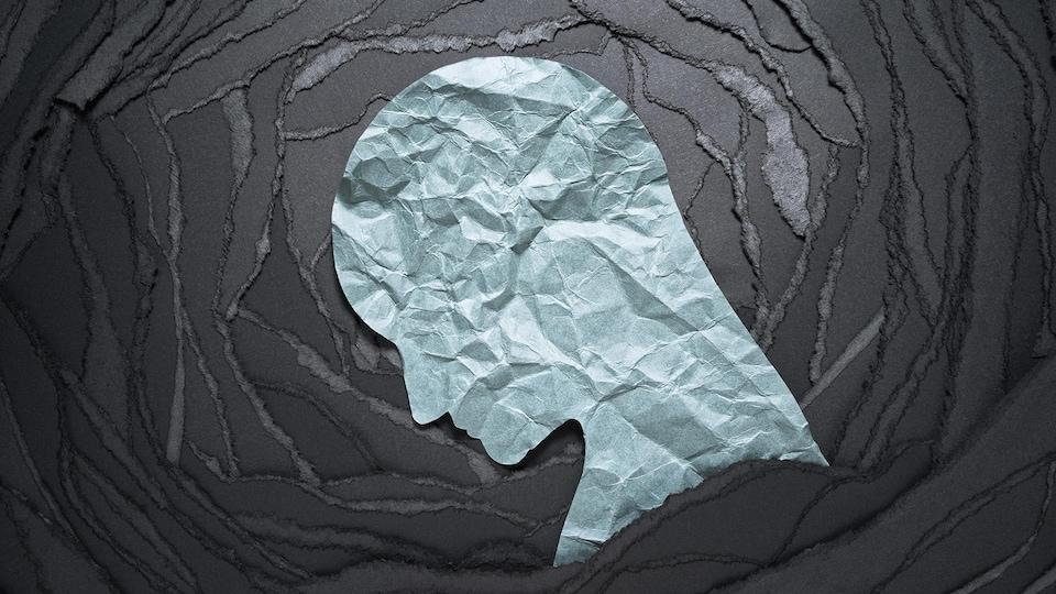 Illustration en papier d'une tête troublée dans un tourbillon noir.