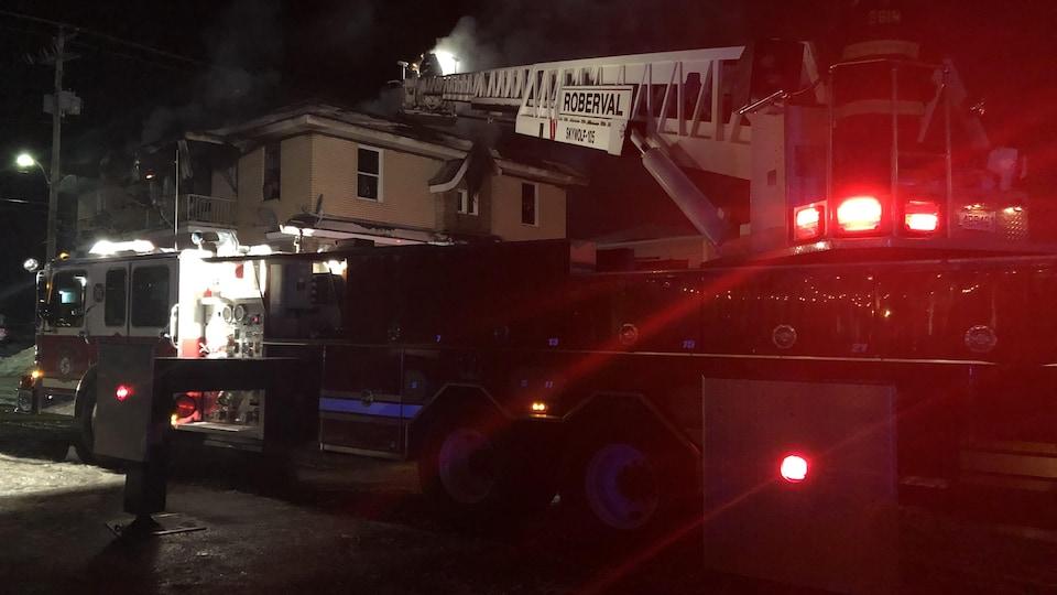 Un camion de pompier devant un immeuble en feu
