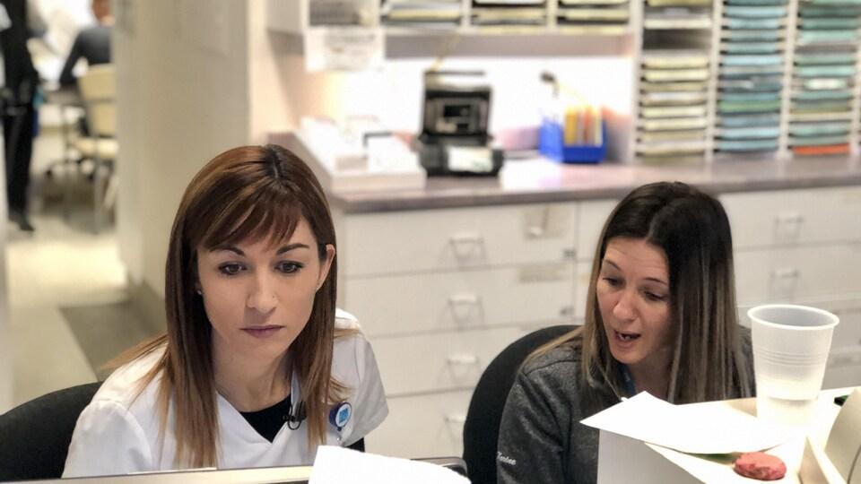L'infirmière discute du dossier d'un patient avec une collègue.