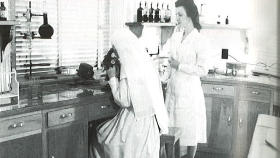 Photo d'une religieuse qui utilise un microscope et d'une infirmière dans un laboratoire