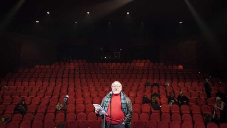 Un homme parle au micro dans une salle de théâtre. Derrière lui, une série de sièges rouges.