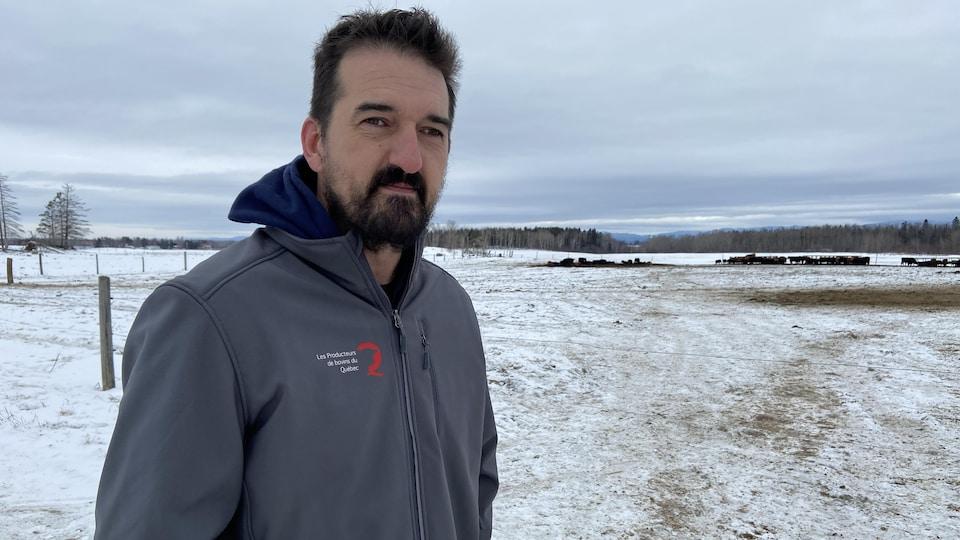 Jean-Thomas Maltais pose devant un champs avec des bovins en arrière-plan.