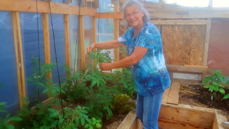 Une femme est debout dans une serre avec des plants de tomates.