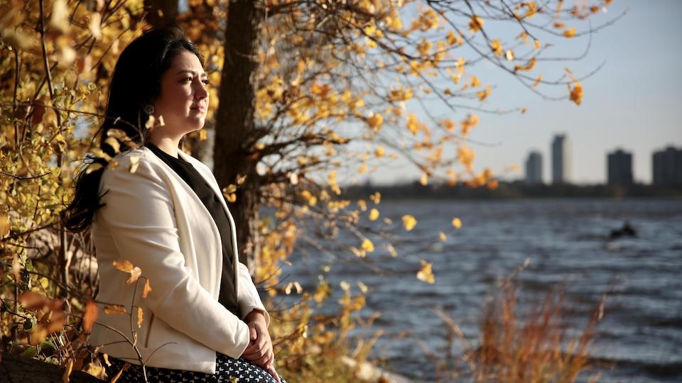 Jessie Nault qui regarde vers la droite, assise au bord d'une rivière.