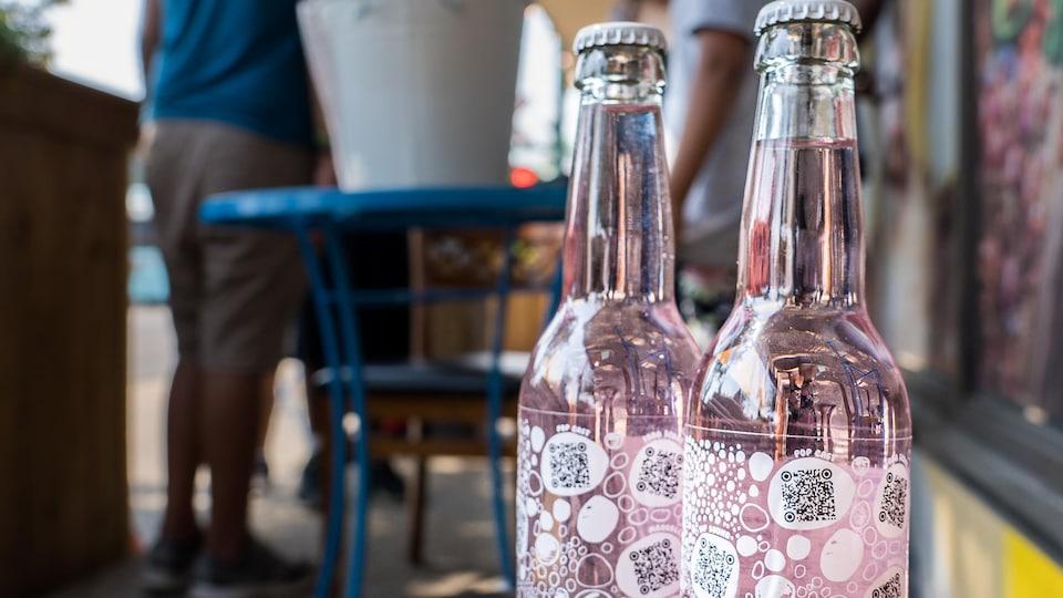 Deux bouteilles de boisson gazeuses sont déposées sur une table.