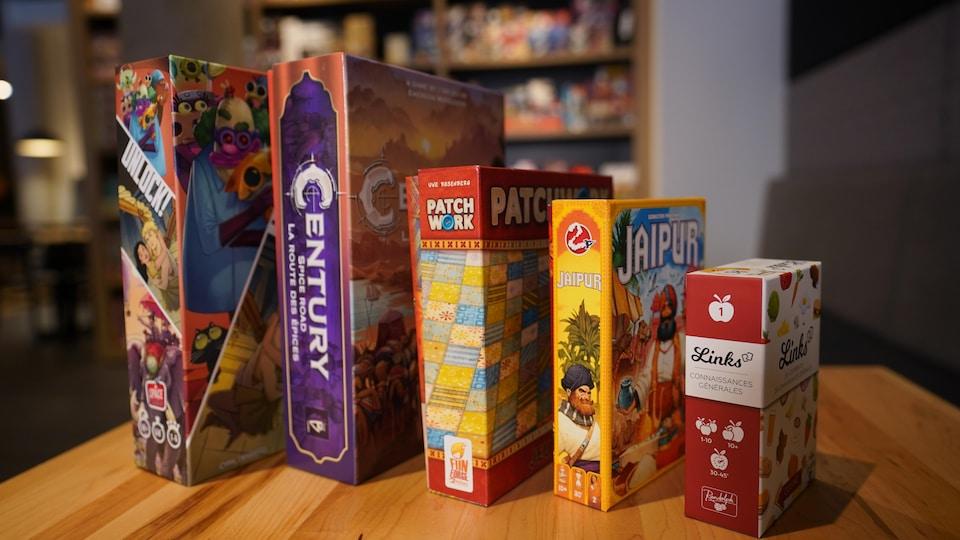 Cinq boîtes de jeux de société posées sur une table.