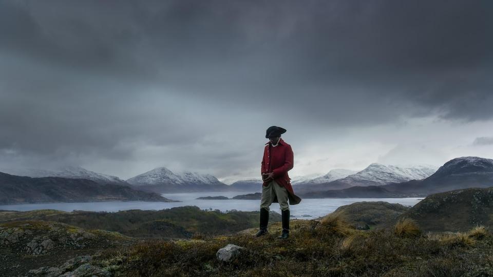 Un homme en habits d'époque dans un paysage nuageux.