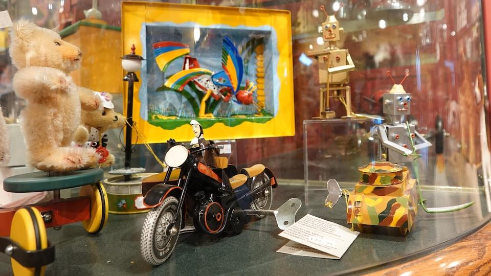 Des jouets mécaniques en métal qui se remontent avec une clé sont exposés dans une vitrine. On voit un mini-tank, une moto et un robot.
