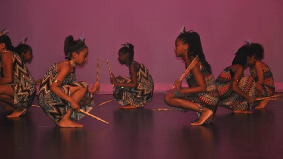 Sept filles accroupies pendant une performance de danse afro-antillaise.