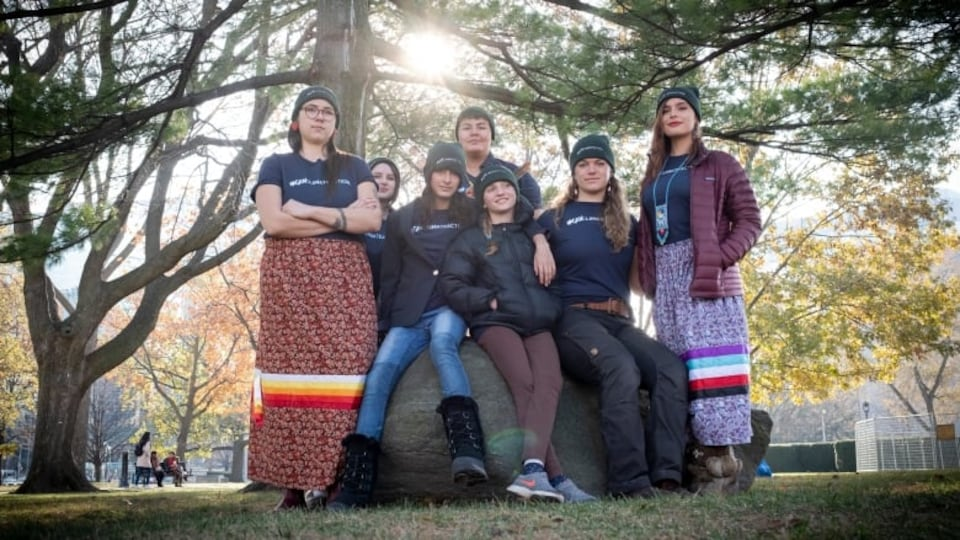 Sept jeunes femmes dont certaines sont assises sur un rocher posent sous l'ombre d'un arbre.