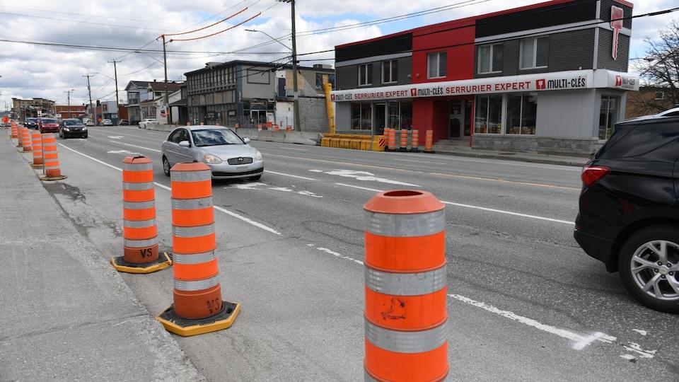 Des cônes sont allignés en bordure de la rue King Ouest devant l'entreprise Multi-Clés serrurier expert. Des véicules circulent.