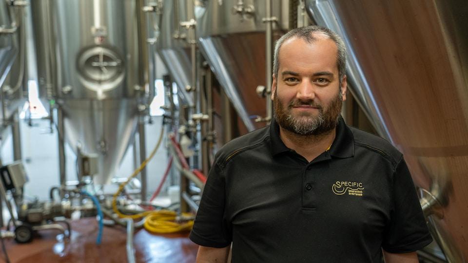 Kirk Zembal au milieu des immenses cuves de bière.