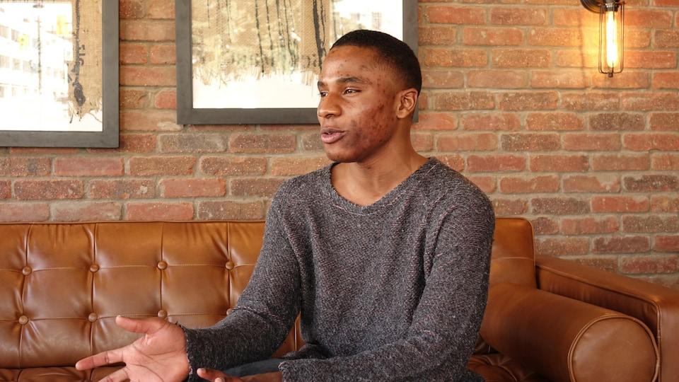 Un homme assis sur un fauteuil de cuir en pleine discussion.