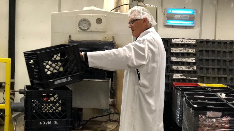 Yvon Pedneault met des caisses de lait dans la machine à laver.
