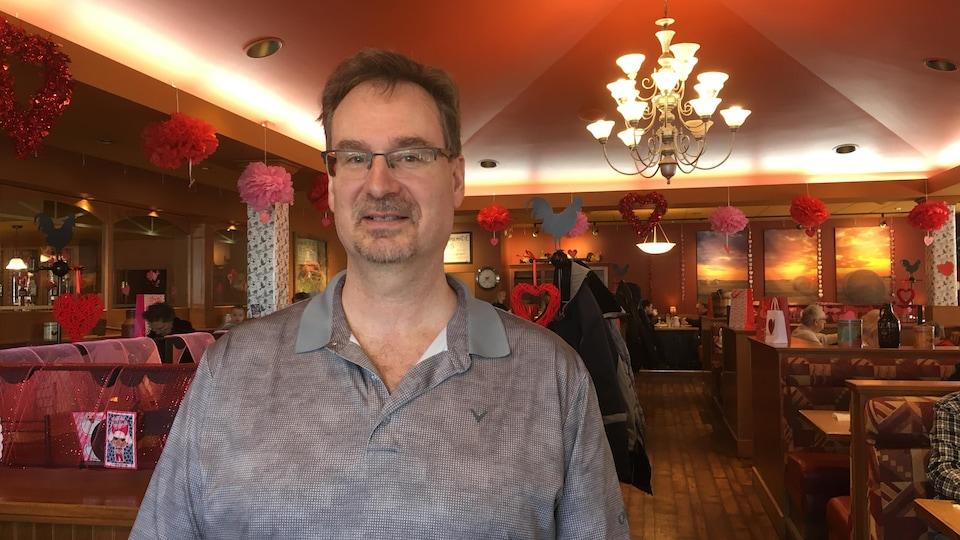 Un homme se tient devant une salle de restaurant décorée de coeurs.