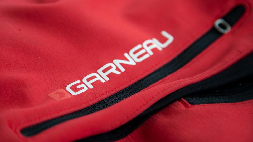 Plan rapproché du logo de la marque Garneau imprimé sur un vêtement de sport de couleur rouge.