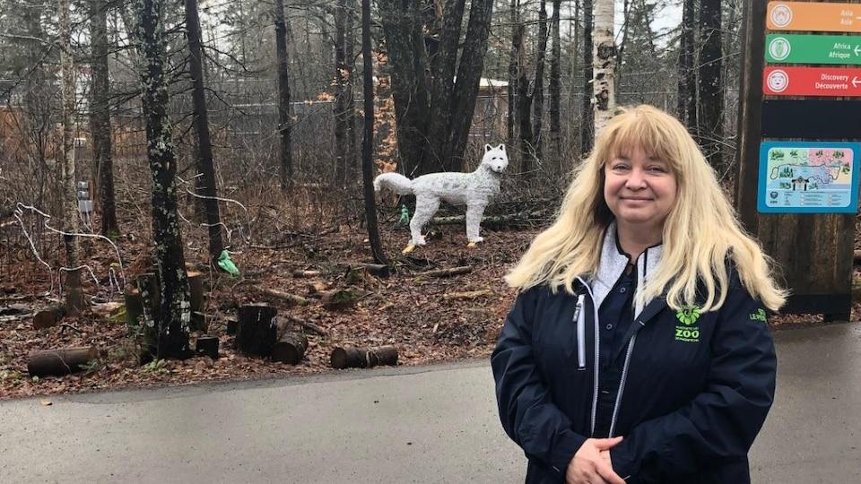Une femme est debout à l'extérieur. En arrière-plan, un boisé et des décorations de loups.
