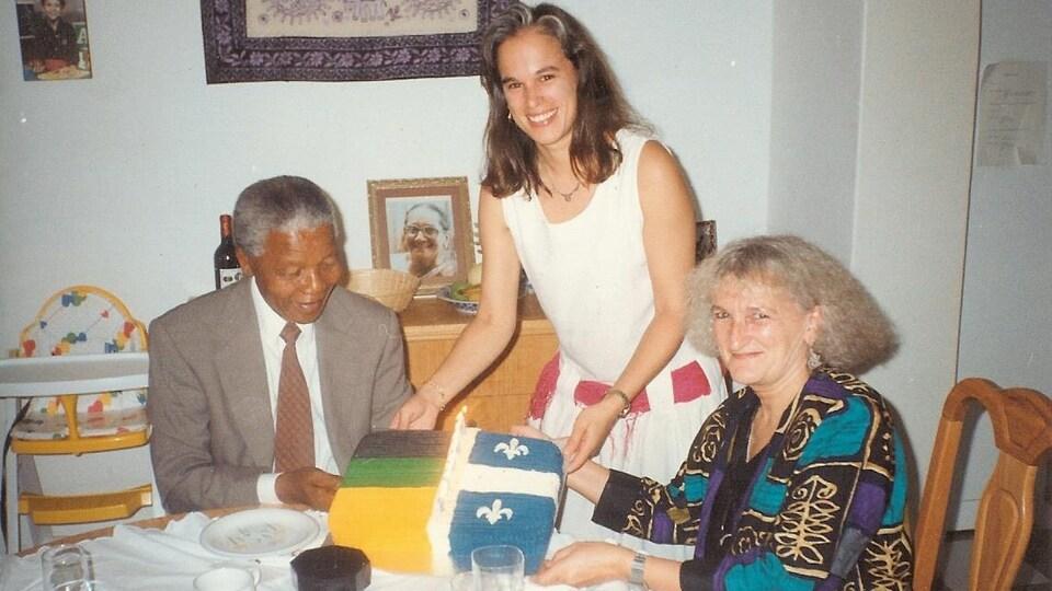 Nelson Mandela, Lucie Pagé et sa mère Louise Grondin assis à une table avec un gâteau.