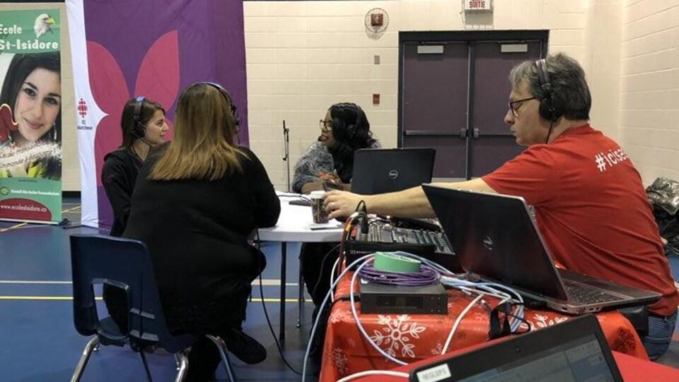 Deux invités parlent à une animatrice de radio devant la bannière de Radio-canada.