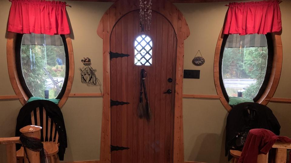 La porte d'entrée, faite de bois et de métal, et les fenêtres ovales de la maison de Nicole Larouche lui donnent un air médiéval.