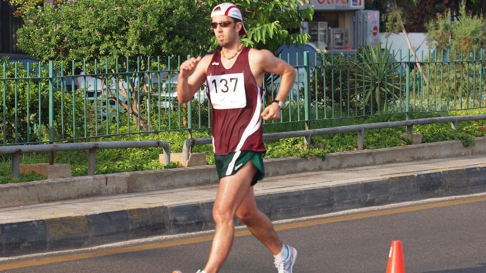 Un homme portant un dossard fait de la marche rapide sur une route.