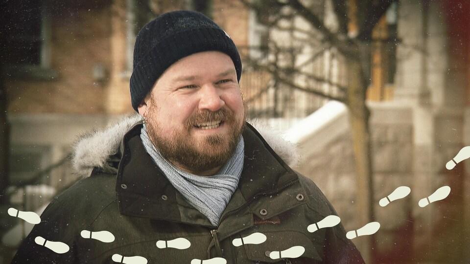 Benjamin Rodger souriant devant un immeuble.