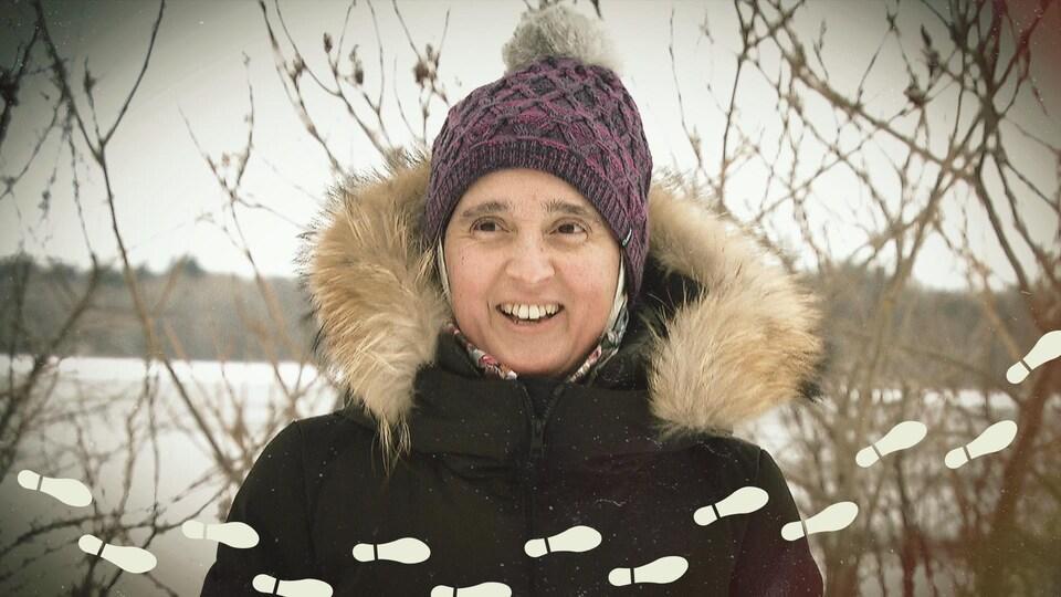 Monia Mazigh en habits d'hiver qui sourit en regardant vers l'objectif.