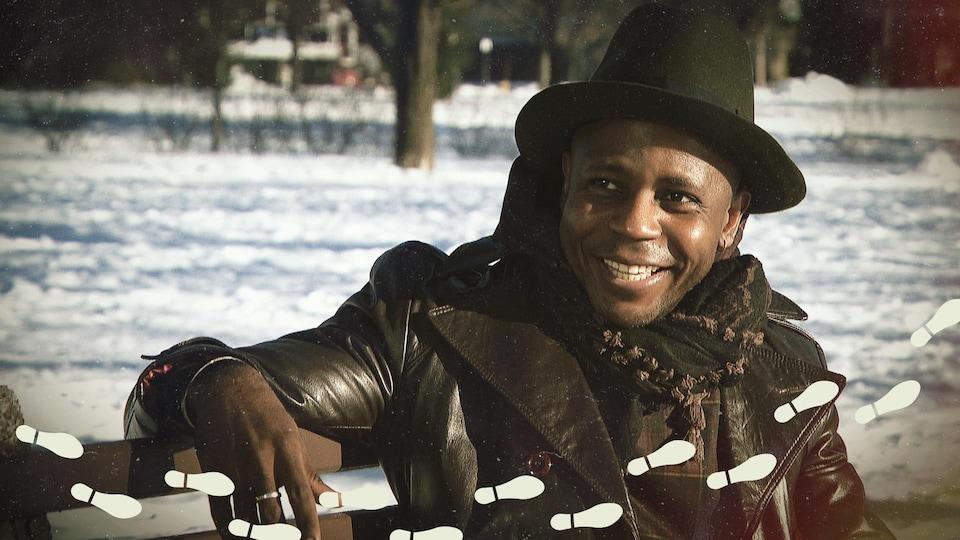 Le R Premier, souriant, assis sur un banc de parc en hiver.