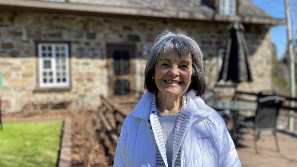 Marie Gendron se trouve devant le moulin.