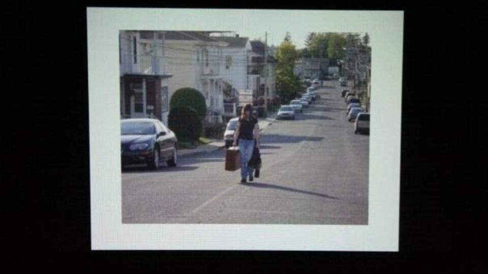 Marie-Lou marche dans la rue avec sa valise
