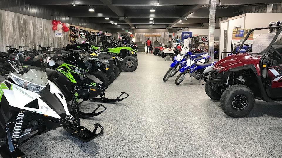 L'intérieur d'un commerce avec des motoneiges et des motos.